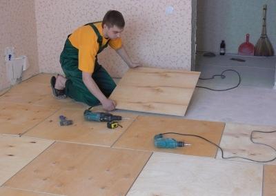 Процесс укладки фанеры на бетонное основание