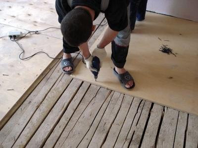 Фанерная подложка на деревянной напольной поверхности