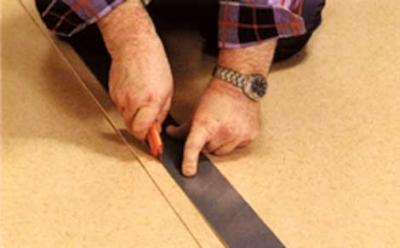 Разрезание двух слоёв линолеума в месте стыка